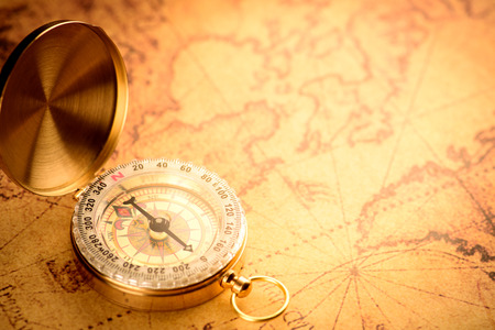azimuth: Old  gold vintage compass on vintage map:Heading south
