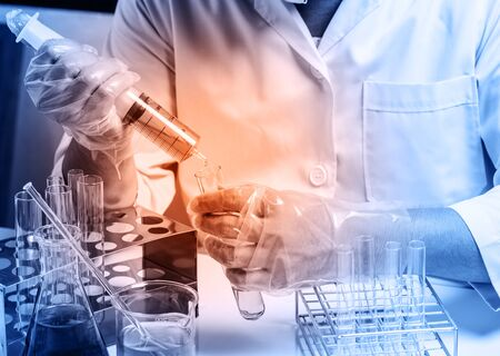 scientist: Conical flask in scientist hand with lab glassware background, Laboratory research concept