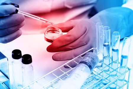 Conical flask in scientist hand with lab glassware background, Laboratory research concept