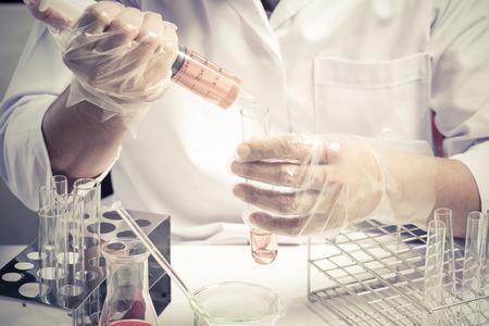 biotecnologia: Frasco c�nico en el cient�fico mano con el fondo de la cristaler�a de laboratorio, el concepto de investigaci�n de laboratorio