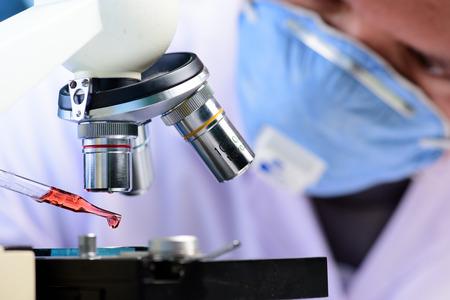 bata de laboratorio: Cient�fico cayendo l�quido qu�mico al microscopio, el concepto de investigaci�n de laboratorio