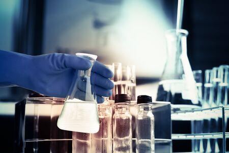 biologia: Frasco de científico mano con el fondo equipo de laboratorio
