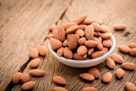 almonds in a white ceramic bowl on grained wood background Imagens