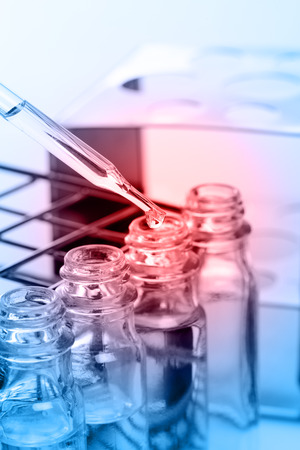 dropping: Dropping chemical liquid to test tubes, laboratory research Stock Photo