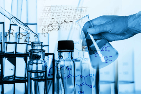 El investigador está cayendo el reactivo en el tubo de ensayo, con las ecuaciones químicas de fondo, en el laboratorio