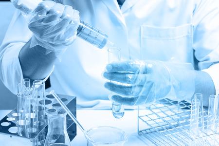 Bottiglia conica in mano di scienziato con background di vetro di laboratorio, concetto di ricerca di laboratorio