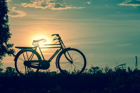 image style: beautiful landscape image with Silhouette Bicycle at sunset in vintage tone style