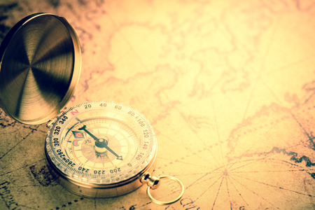 treasure: Old  gold vintage compass on vintage map:Heading south