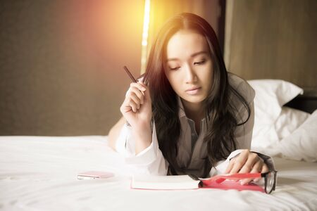 Beautiful asian woman thinking for writing notes she is lying on the bed