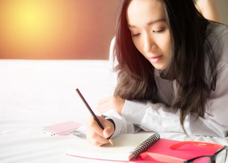 Schöne asiatische Frau, die Schreiben von Notizen auf dem Bett liegend