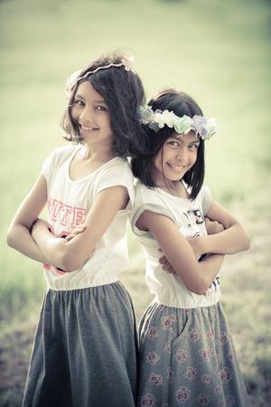 ni�as peque�as: Imagen del retrato de dos ni�as gemelas que juegan en la granja; estilo de tono de �poca Foto de archivo