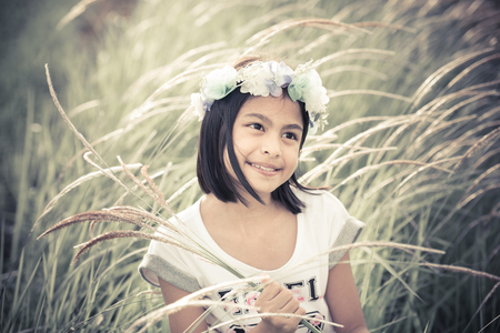 girl looking up: Beautiful asian girl holding glass flowers in a farm;vintage tone style Stock Photo
