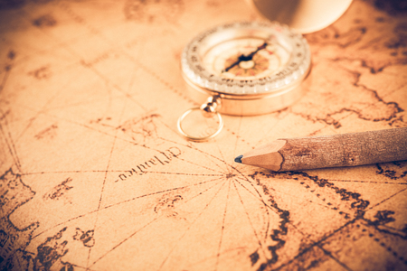 azimuth: Old  gold vintage compass and pencil on vintage map;vintage tone style Stock Photo