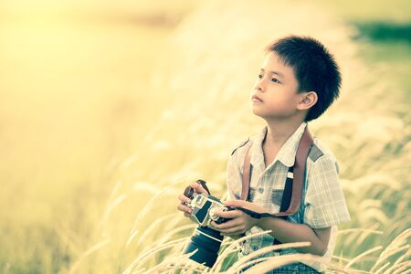 nature photo: asian boy with classic camera is shooting in the farm;vintage filter