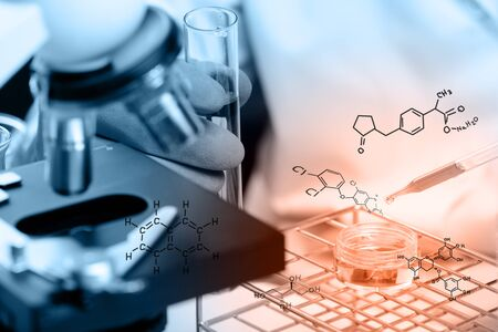 clinician: Hands of clinician holding tools during scientific experiment ,Hands of clinician holding tools during scientific experiment ,Researcher is dropping the reagent into test tube, with chemical equations background, in laboratory
