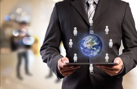 small world: Business man holding tablet pc with business people icons around the small world  Stock Photo