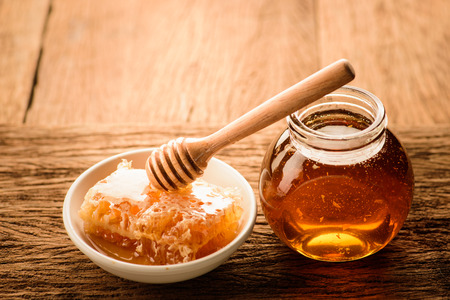 Honey with wooden honey dipper and ceramic bowl honeycomb background