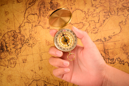 azimuth: Close up of the hand holding a vintage compass over a vintage map