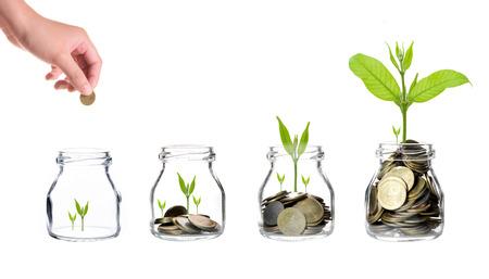Mão da mulher com moedas de mistura e semente em garrafa clara no fundo branco, conceito de crescimento de investimento de negócios, conceito de economia Imagens