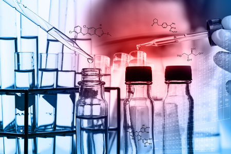 A researcher is testing, dropping reagent to test tube at laboratory with chemical equations and periodic table background.