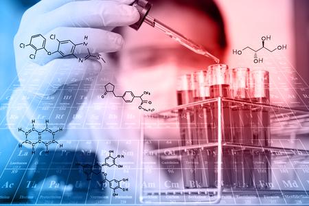 investigador es la prueba, dejando caer reactivo para tubo de ensayo en el laboratorio con las ecuaciones químicas y tabla periódica background.Man lleve gafas de protección
