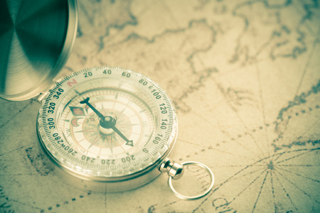 Old  gold vintage compass on vintage map:Heading south ;vintage tone style
