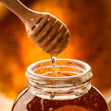 drizzler: jar of honey with wooden drizzler on honeycomb background