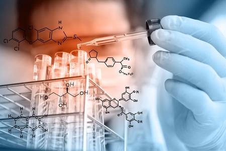 tubo de ensayo: Pipeta con gota de líquido en tubos de ensayo de vidrio para un experimento en un laboratorio de investigación en ciencias.