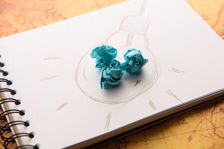 metaphor: Inspiration concept crumpled paper with light bulb metaphor for good idea