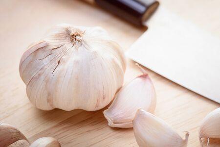 garlic clove: garlic and knife on wood block Stock Photo
