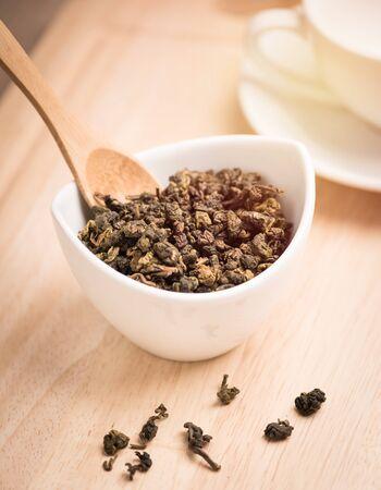 dry leaf: dry tea leaf in ceramic bowl on wood background