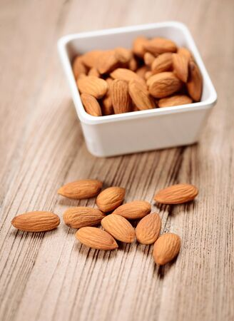 grained: close up of some almonds in a white ceramic bowl on grained wood background