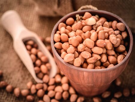 earthnuts: close up of raw peanuts or arachis in wood scoop on sack background Stock Photo