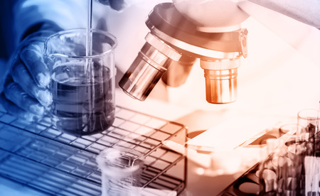 instrumental medico: cient�fico cayendo l�quido qu�mico en el matraz con el estilo de la doble exposici�n microscopio