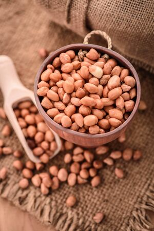 arachis: close up of raw peanuts or arachis in wood cup on sack background