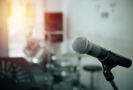 Closeup of microphone in music studio blurred background,vintage tone style Imagens