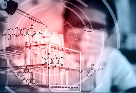 Pipeta com gota do líquido amarelo sobre tubos de ensaio de vidro para uma experiência em uma ciência de pesquisa .Scientists laboratório No laboratório com a equação química