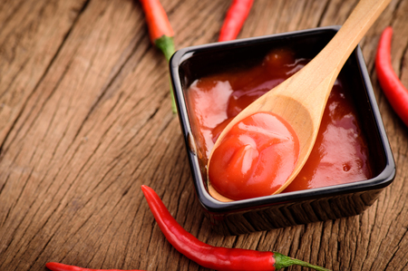 chilli sauce: Red hot chilli sauce in wood spoon