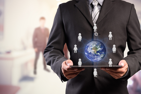 small world: Business man holding tablet pc with businesspeople icons around the small world (Elements of this image furnished by NASA) Stock Photo