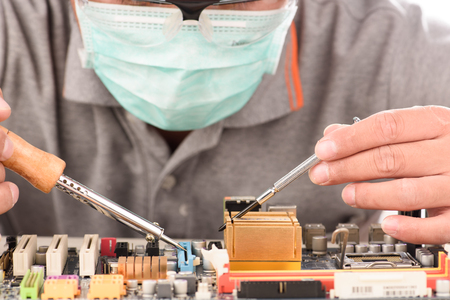 technology tool: Technological background with closeup on tester checking motherboard. Electronics repair service, hands of female tech fixes an electronic circuit,computer technology concept