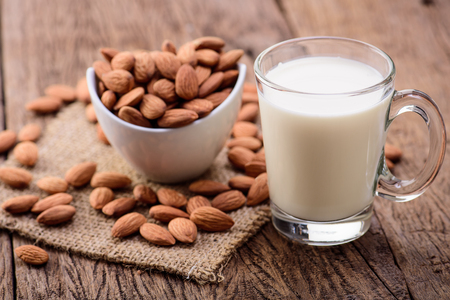 drinking milk: Almond milk in glass with almonds