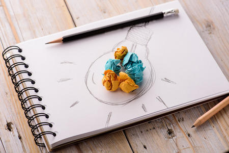 良いアイデアのための電球のメタファーと紙をくしゃくしゃにインスピレーションのコンセプト