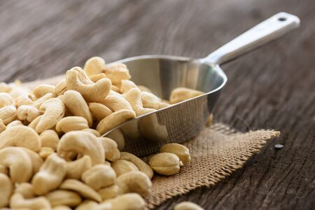 protein crops: raw cashew nuts with stainless spoon on wood table