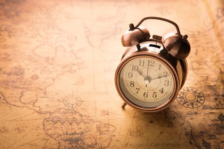 desaturated: Classic Alarm clock on vintage map background