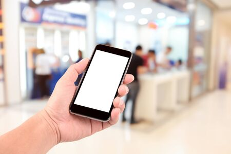 counter service: female hand holding the phone tablet on blurred in shop counter service background;Transactions by phone concept