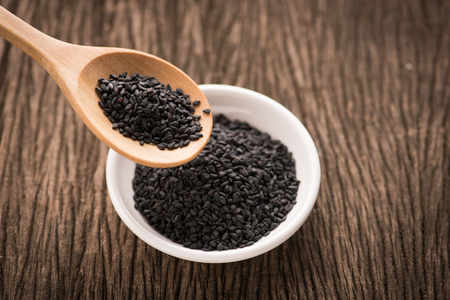 black Sesame close up shot in wood spoon  on wood background