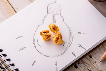 metaphors: Inspiration concept crumpled paper with light bulb metaphor for good idea