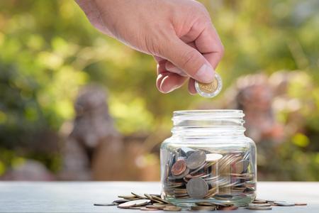 Mano ahorro de dinero de las monedas en la hucha de vidrio con fondo verde bokeh en el concepto de ahorro de dinero