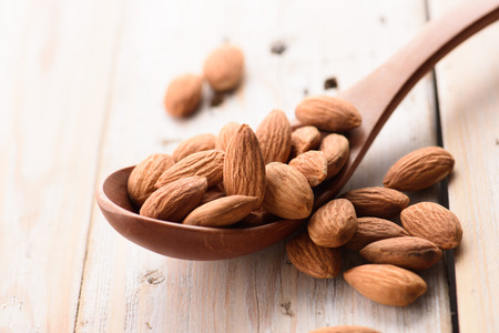 Almonds pour from wood spoon