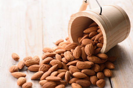 nutshells: Almonds pour from wood bucket Stock Photo
